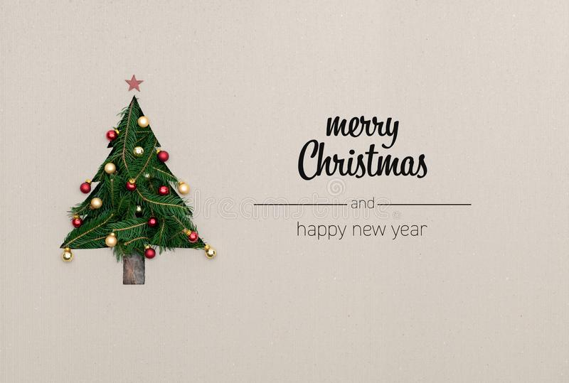 Merry Christmas and happy new year greetings in vertical top view cardboard with natural eco decorated christmas tree. Pine.Ecology concept.Xmas winter holiday stock photography