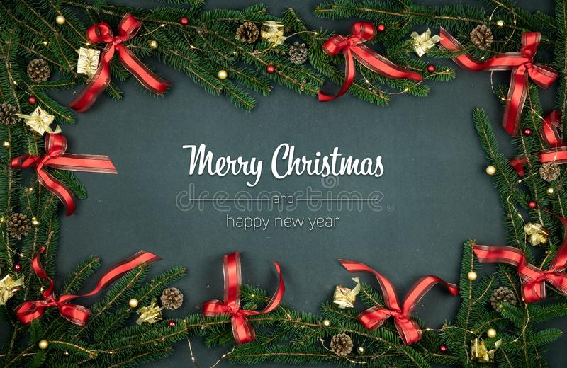 Merry Christmas and happy new year greetings in vertical top view dark blackboard with pine branches,ribbons and lights. Decorated frame.Xmas winter holiday stock images