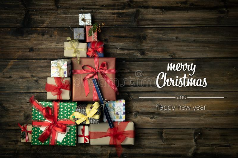 Merry Christmas and happy new year greetings in vertical top view dark vintage wood with christmas tree pine made of. Gift present boxes.Xmas winter holiday stock image