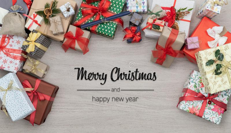 Merry Christmas and happy new year greetings in vertical top view wooden table full of christmas gifts presents.Xmas stock image