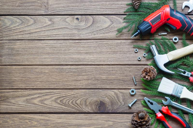 Merry Christmas and Happy new year handy construction tools back. Ground concept. Hammer, wrenches, screwdriver, pliers, paint brush, pine leaves, pine cones stock photos