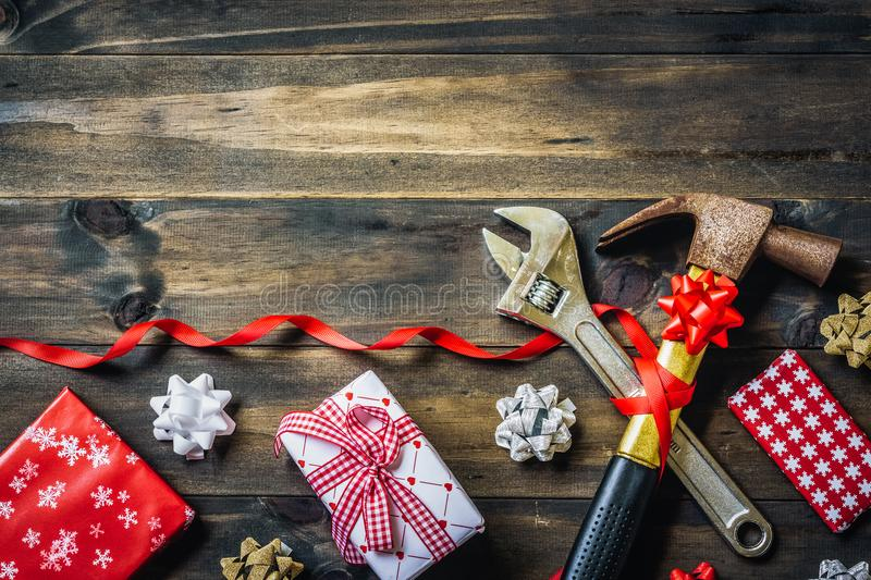 Merry christmas and Happy New year with handy tools background. Concept, Used old rusty hammers and adjustable wrench with gifts and bows decoration on wood top royalty free stock photography