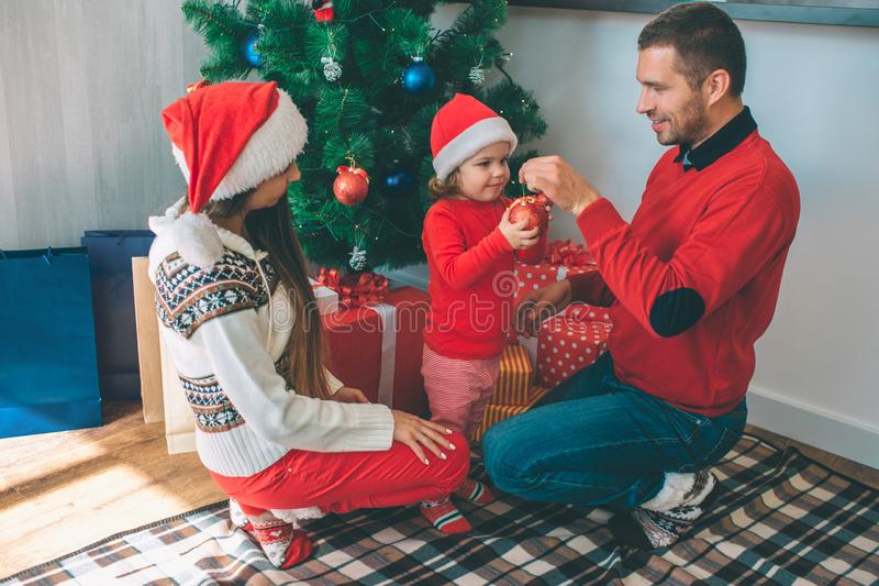 Merry Christmas and Happy New Year. Happy family sitting together at Christmas tree. Young man hold top of red toy while. Merry Christmas and Happy New Year stock photos