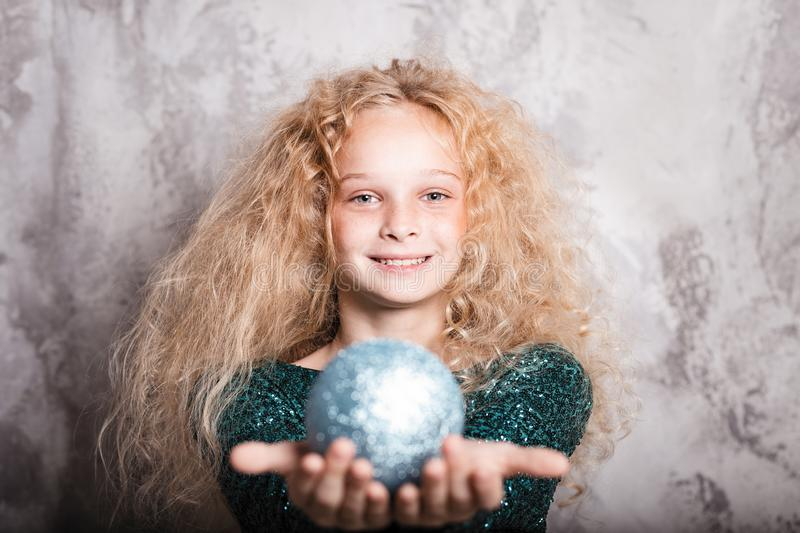 Merry Christmas and happy new year! happy girl with big ball toy in hands looks very pleased. Close portrait. Merry Christmas and happy new year! happy girl with royalty free stock images