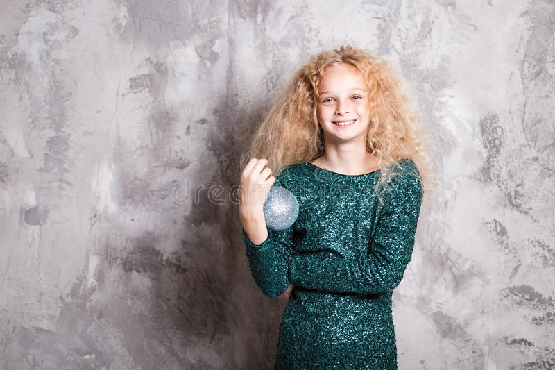 Merry Christmas and happy new year! happy girl with big ball toy in hands looks very pleased. Close portrait. Merry Christmas and happy new year! happy girl with royalty free stock photography