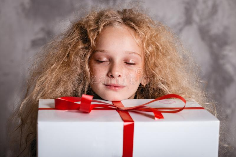 Merry Christmas and happy new year! happy girl with big present in hands closed eyes dreaming about something. Close portrait. Merry Christmas and happy new year stock images