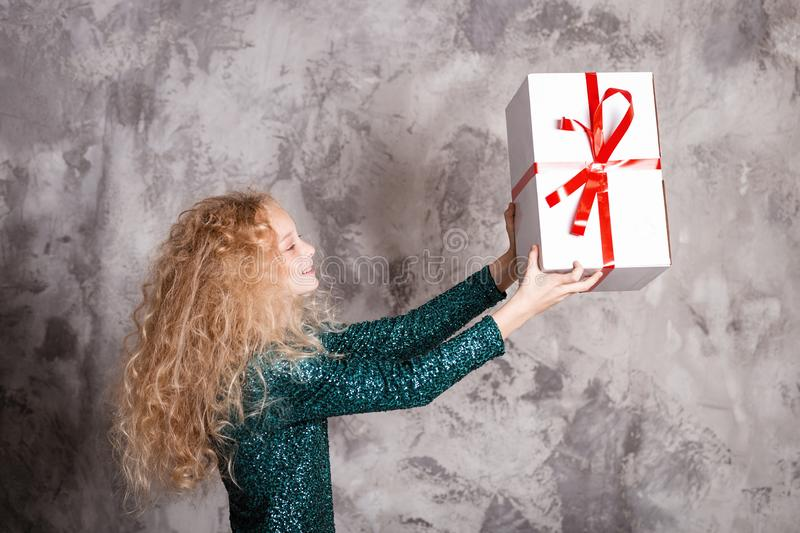 Merry Christmas and happy new year! happy girl with big present in hands looks very pleased. Close portrait. Merry Christmas and happy new year! happy girl with stock photos