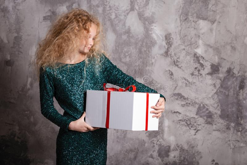 Merry Christmas and happy new year! happy girl with big present in hands thinking about gift. Merry Christmas and happy new year! happy girl with big present in royalty free stock image