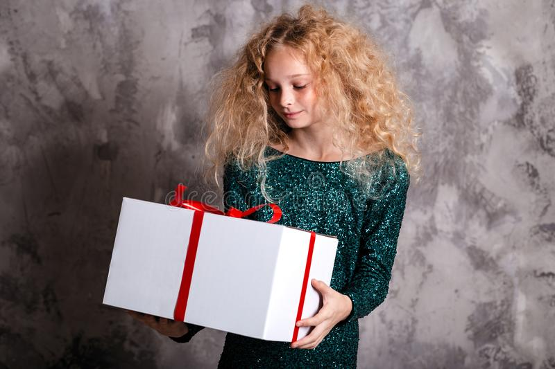 Merry Christmas and happy new year! happy girl with big present in hands thinking about gift. Merry Christmas and happy new year! happy girl with  big present in royalty free stock photography