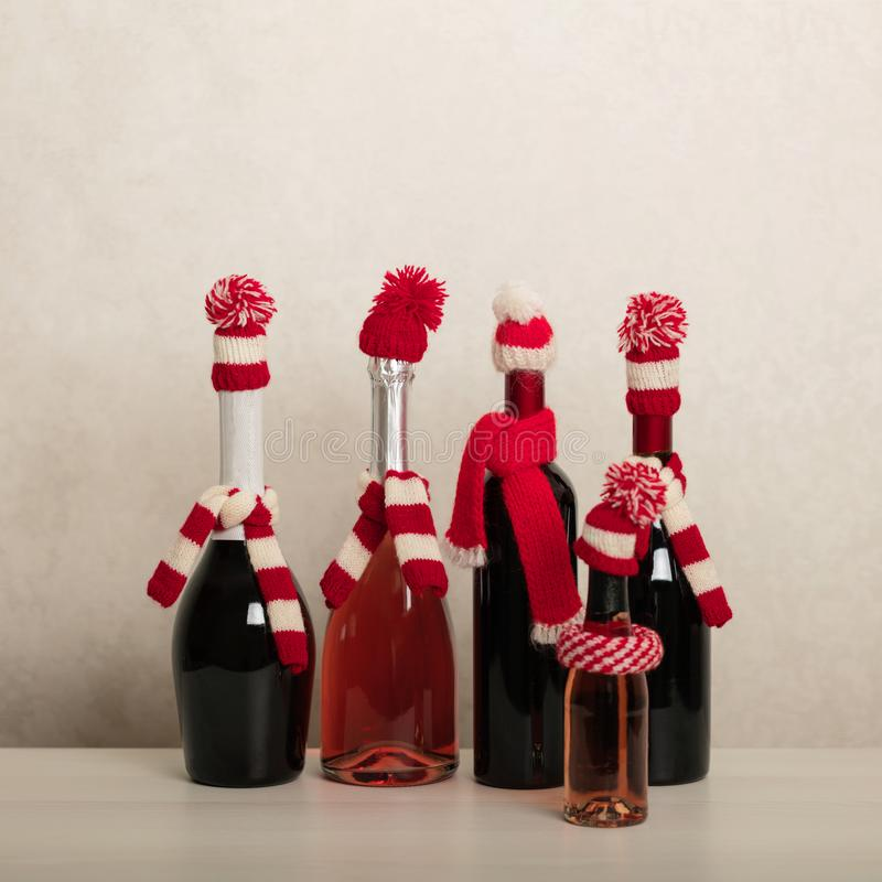Merry Christmas and Happy New Year! Holiday knitted decor - Santa Claus knitted hats on the bottle with wine. Selective focus royalty free stock photos