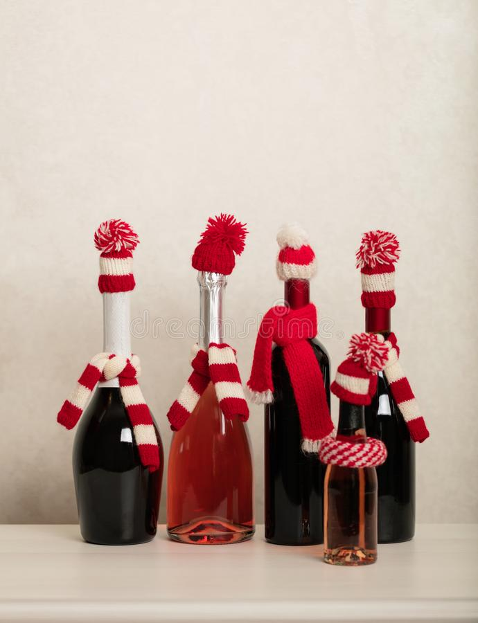 Merry Christmas and Happy New Year! Holiday knitted decor - Santa Claus knitted hats on the bottle with wine. Selective focus stock image