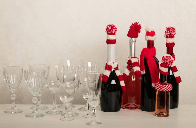 Merry Christmas and Happy New Year! Holiday knitted decor - Santa Claus knitted hats on the bottle with wine. Selective focus stock photography