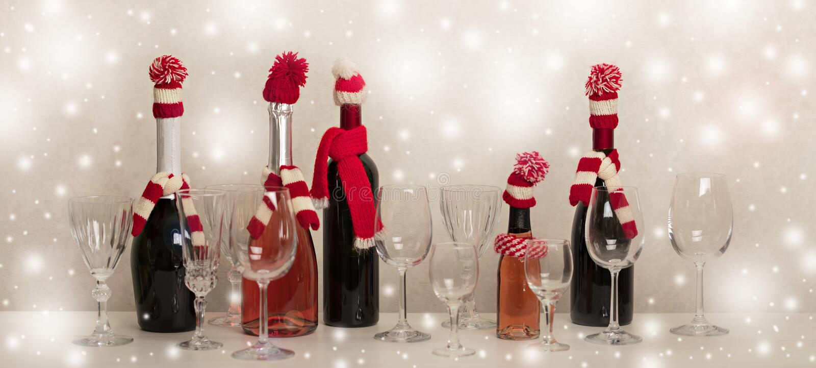 Merry Christmas and Happy New Year! Holiday knitted decor - Santa Claus knitted hats on the bottle with wine. Selective focus royalty free stock image