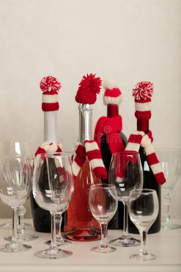 Merry Christmas and Happy New Year! Holiday knitted decor - Santa Claus knitted hats on the bottle with wine. Selective focus stock photo