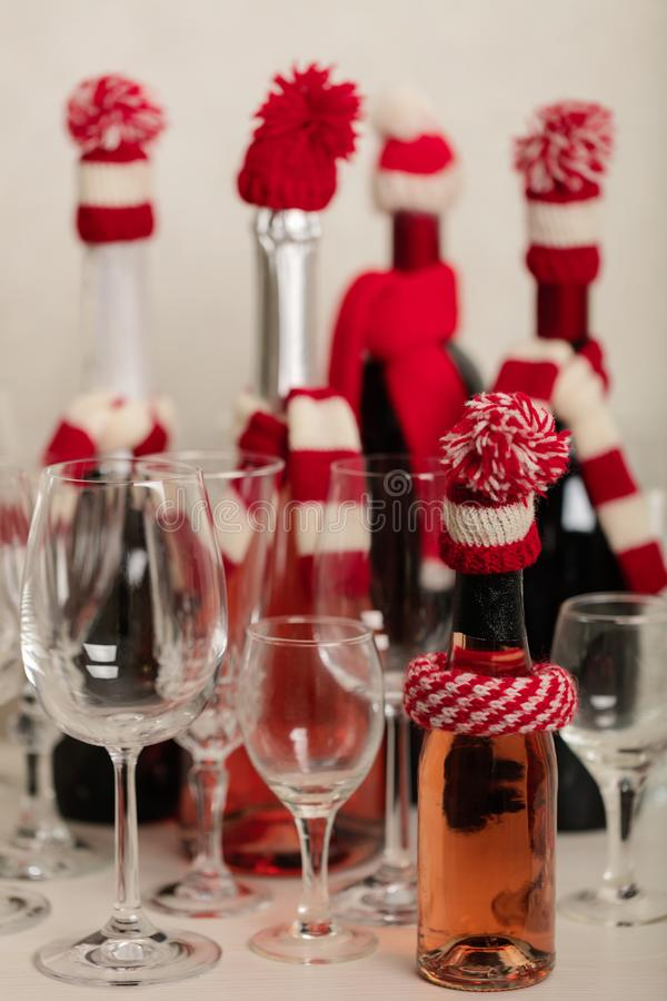 Merry Christmas and Happy New Year! Holiday knitted decor - Santa Claus knitted hats on the bottle with wine. Selective focus royalty free stock photo
