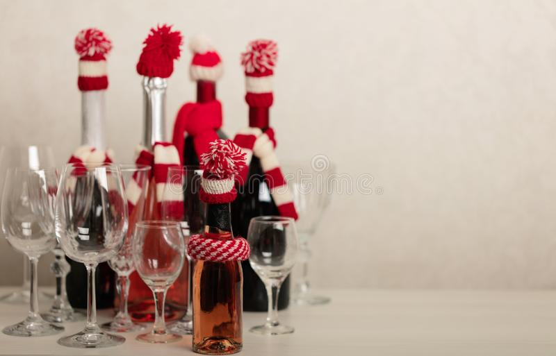 Merry Christmas and Happy New Year! Holiday knitted decor - Santa Claus knitted hats on the bottle with wine. Selective focus stock images