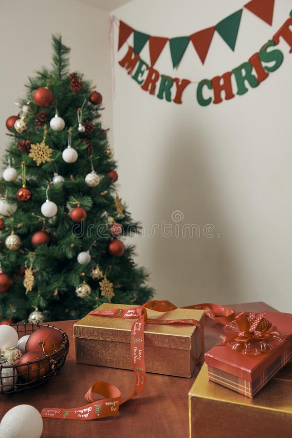 Merry Christmas and Happy New year Holidays! Decorating the Christmas tree indoors. Macro or close picture of xmas tree and gifts stock photo