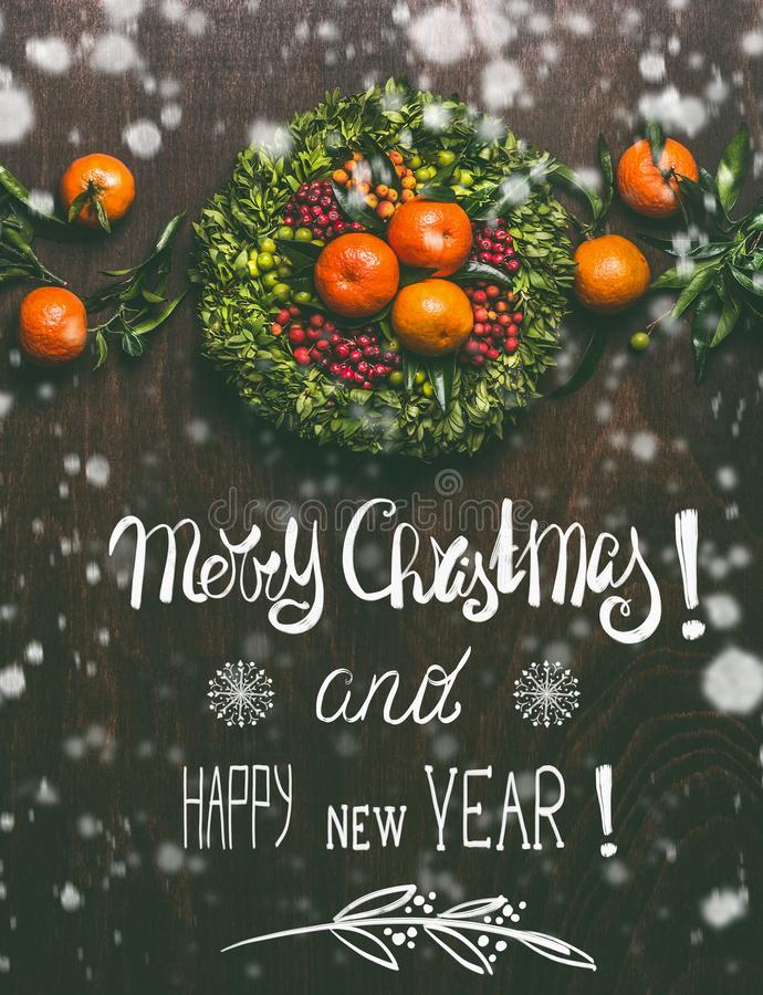 Merry Christmas and Happy New Year lettering greeting card with painted snow and tangerines garland royalty free stock photography