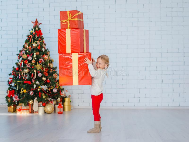 A little girl has a lot of gifts on a white brick wall background. royalty free stock images