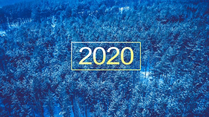 Merry Christmas and Happy New Year 2020. Background with winter forest aerial and numbers twenty twenty stock photography