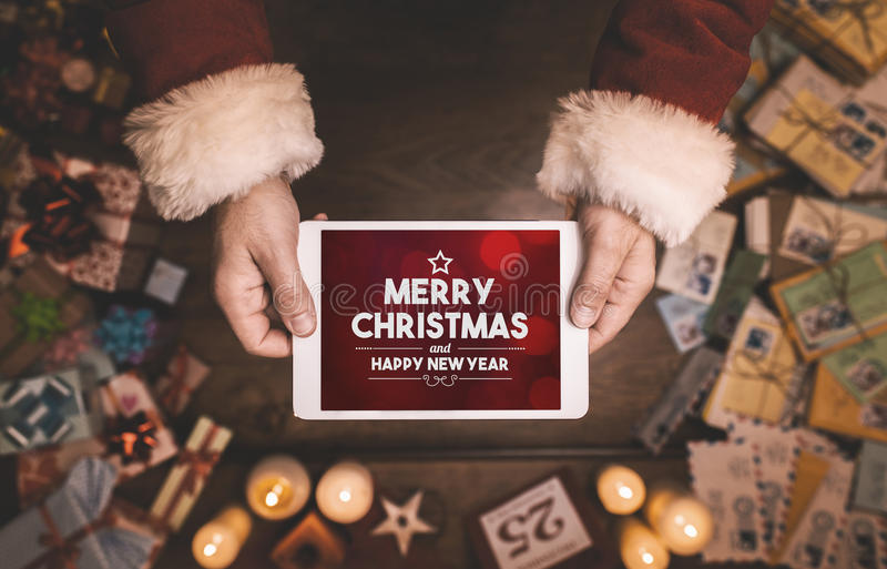 Merry Christmas and Happy New Year message. Santa Claus using a digital touch screen tablet with Merry Christmas and Happy New Year message, hands close up stock image