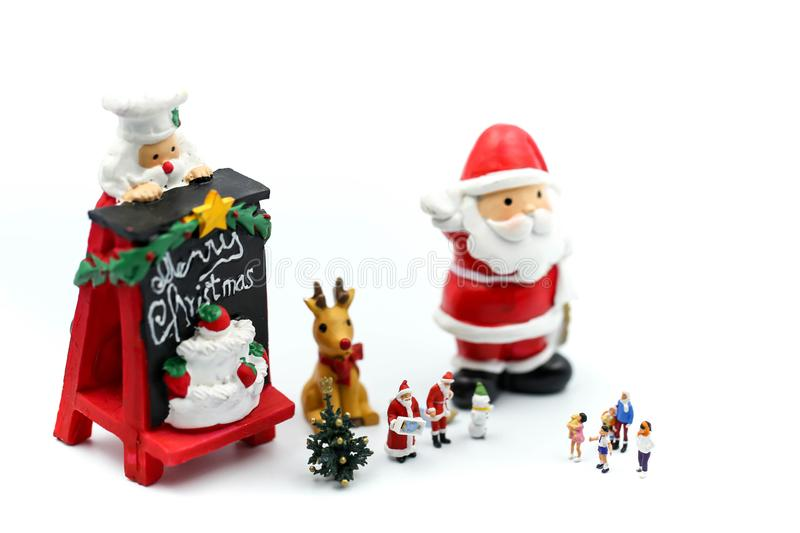 Merry christmas and happy new year Miniature People : Children w. Ith Santa Claus doll and his reindeer isolated on white background,in Christmas festival stock photos