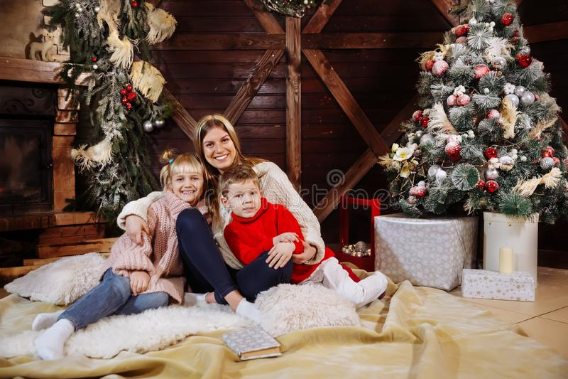 Merry Christmas and Happy New Year. Momand children having fun near Christmas tree indoors near Christmas tree. Merry Christmas and Happy New Year stock photo