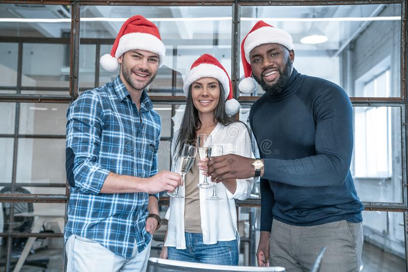 Merry Christmas and Happy New Year 2020. Multiracial young creative people are celebrating holiday in modern office. Group of stock image