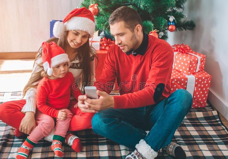 Merry Christmas and Happy New Year. Nice family sits together at Christmas tree. Man holds phone in hands and shows it. To women and child. They are royalty free stock images