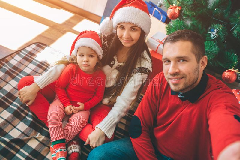 Merry Christmas and Happy New Year. Picture of nice family. Young man hold camera and takes selfie. All of them pose royalty free stock photos