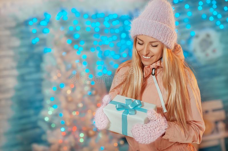 Merry Christmas and Happy New Year! Portrait of happy cheerful beautiful woman in knitted hat mittens holding holiday present box. On Christmas background royalty free stock photography