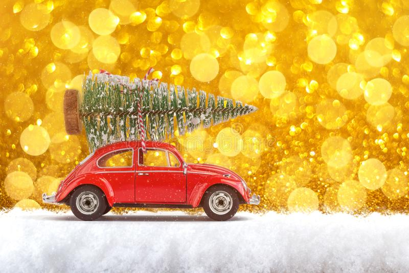 Merry Christmas and Happy New Year Postcard or Poster. Little classic red car carrying Christmas tree on its rack on the. Background of gold spangles. Copy stock photography