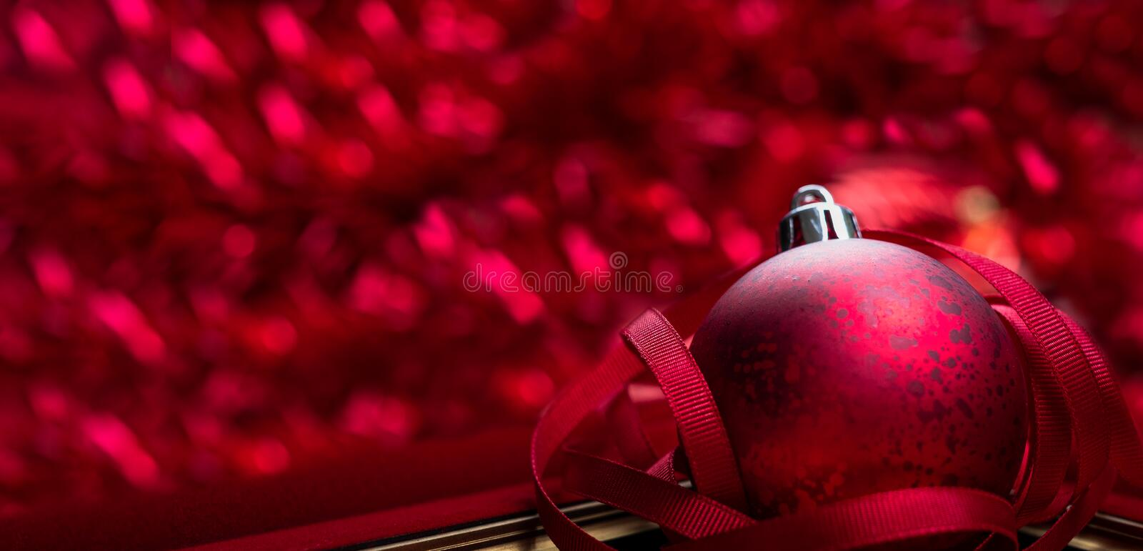 Merry christmas and happy new year red background.close up red decoration ball with blur tinsel at background.holiday celebration royalty free stock photography