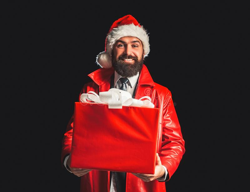 Merry Christmas and Happy New Year. Santa claus with red Christmas gift box. Bearded modern santa on black background. Wishes Merry christmas and Happy new year royalty free stock photo