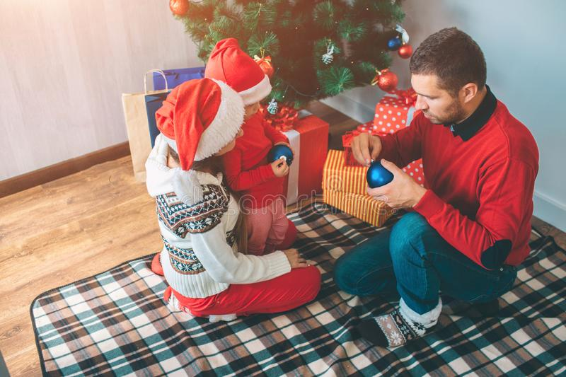 Merry Christmas and Happy New Year. Serious and concentrated members of family hold two blue toys. They are going to put. Them on Christmas tree. Family is on royalty free stock photos