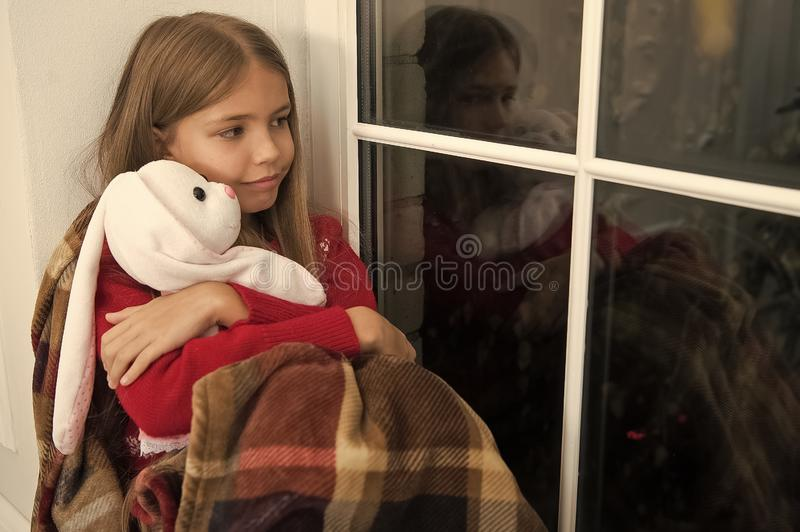Merry Christmas and happy new year. Small child with rabbit toy at window. Small girl hold toy friend. Little child. Relax on Christmas eve. Little girl enjoy royalty free stock image