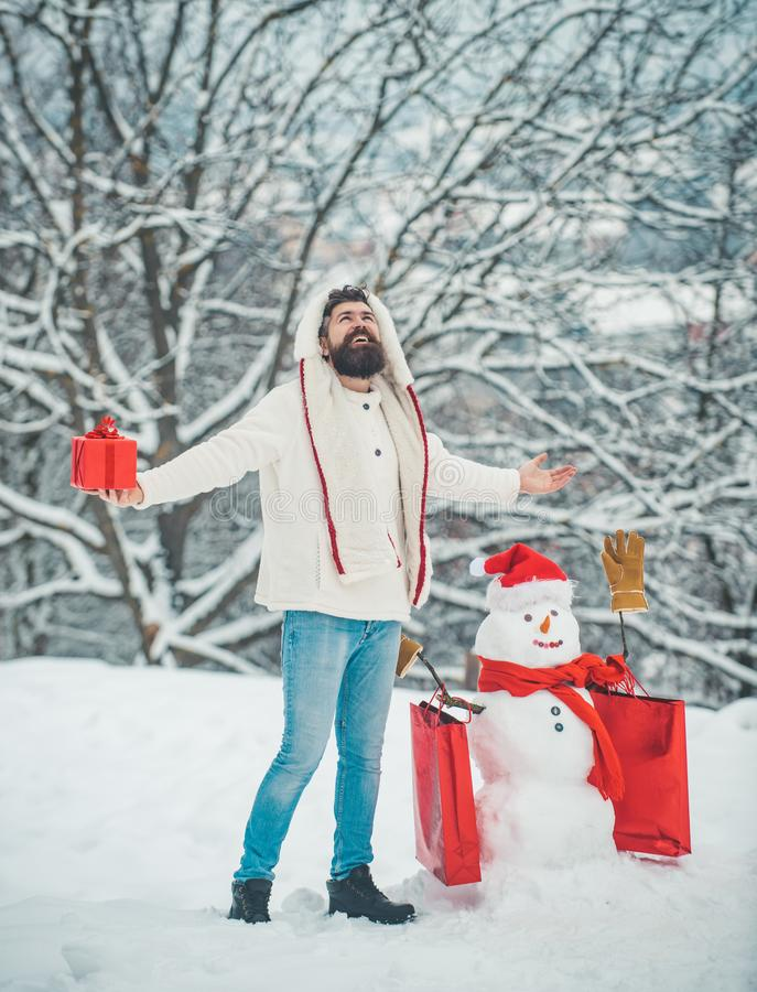 Merry Christmas and Happy new year. Styling Santa hipster with a long beard posing on the Christmas snow background. stock photo