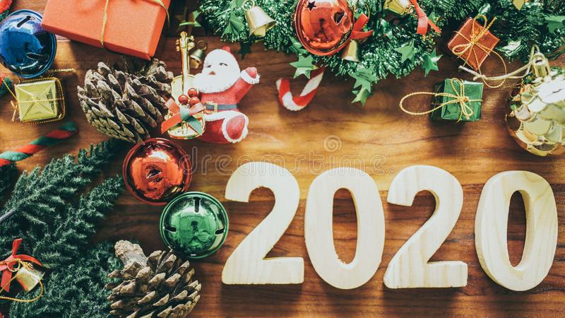 Merry Christmas and Happy New Year 2020 symbols and  Santa Claus, gift, bell miniature on wooden table background stock photo