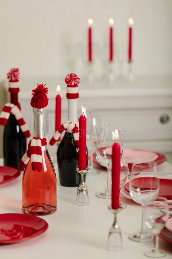 Merry Christmas and Happy New Year! Table setting - red and pink dishes, holiday knitted decor - Santa Claus knitted hats on the. Bottle with wine, red candles royalty free stock photography
