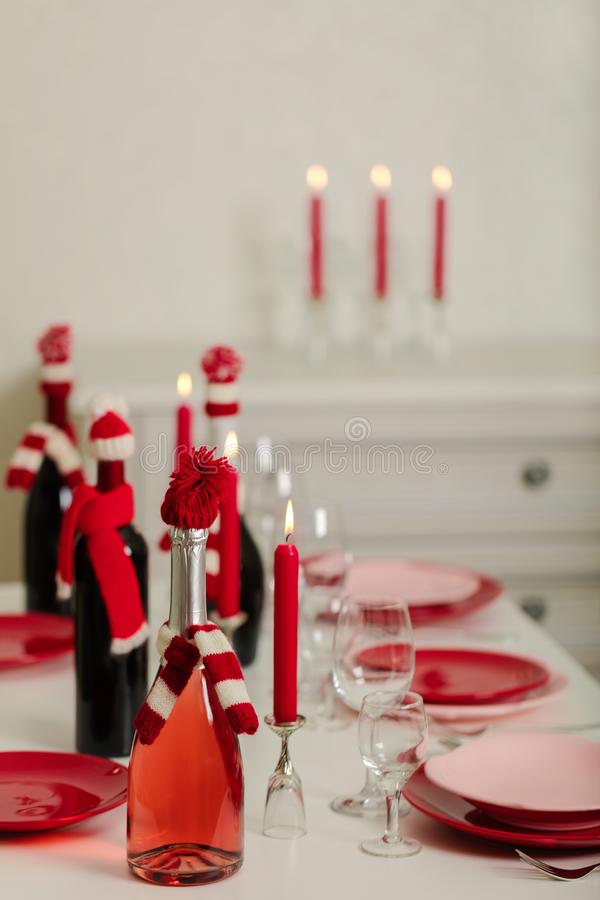 Merry Christmas and Happy New Year! Table setting - red and pink dishes, holiday knitted decor - Santa Claus knitted hats on the. Bottle with wine, red candles stock images