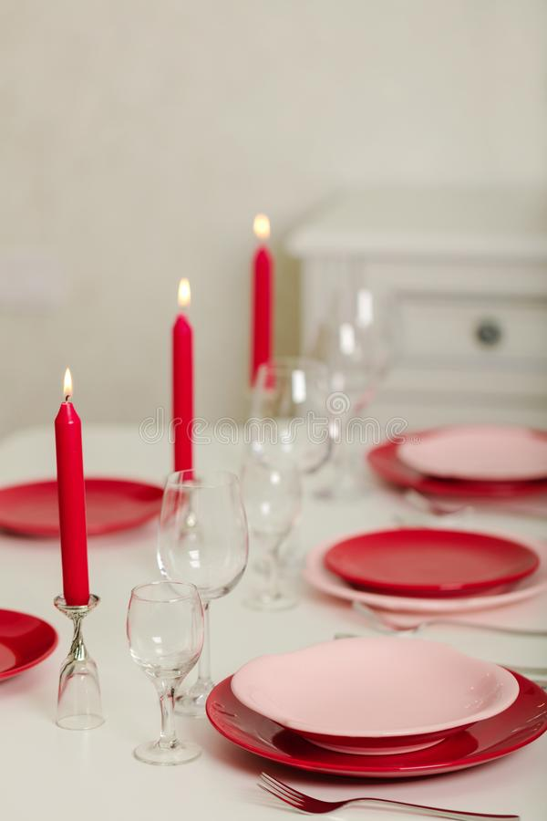 Merry Christmas and Happy New Year! Table setting - red and pink dishes, holiday knitted decor - Santa Claus knitted hats on the. Bottle with wine, red candles stock photos