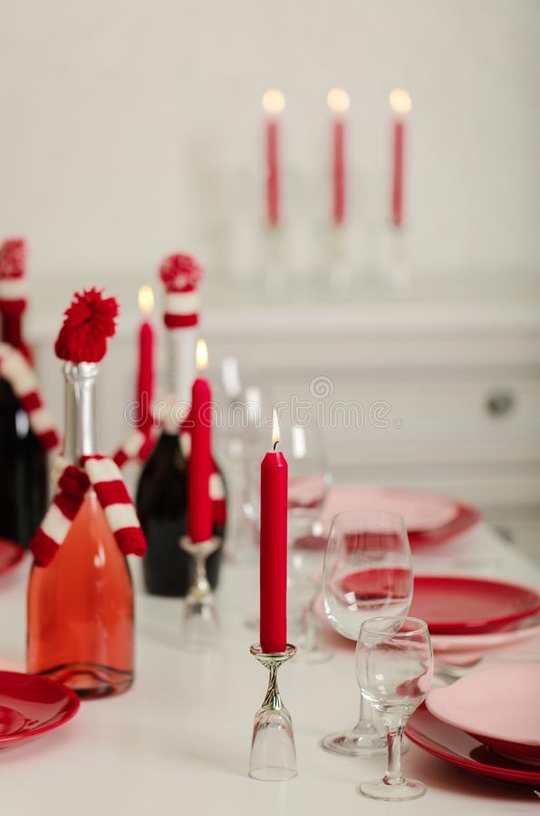 Merry Christmas and Happy New Year! Table setting - red and pink dishes, holiday knitted decor - Santa Claus knitted hats on the. Bottle with wine, red candles stock photo