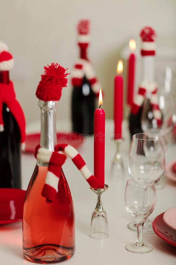 Merry Christmas and Happy New Year! Table setting - red and pink dishes, holiday knitted decor - Santa Claus knitted hats on the. Bottle with wine, red candles stock image