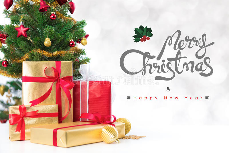 Merry Christmas and Happy New Year text with gift boxes and ornaments. In white bokeh background stock photo