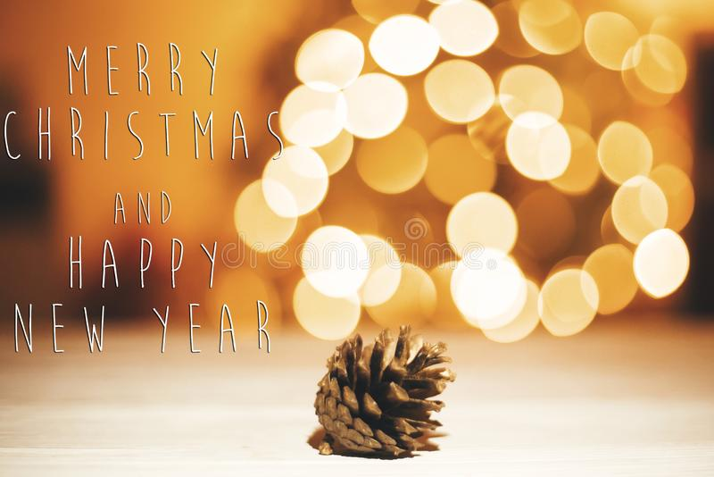 Merry Christmas and Happy New Year text on golden pine cone on w stock image