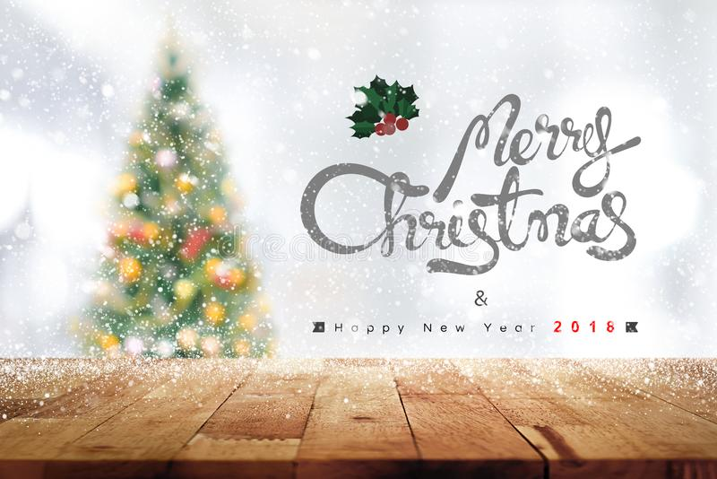 Merry Christmas and Happy New Year 2018 texts above wood table t. Op with a blurred pine tree and snow falling in background - can be used for display or montage royalty free stock images