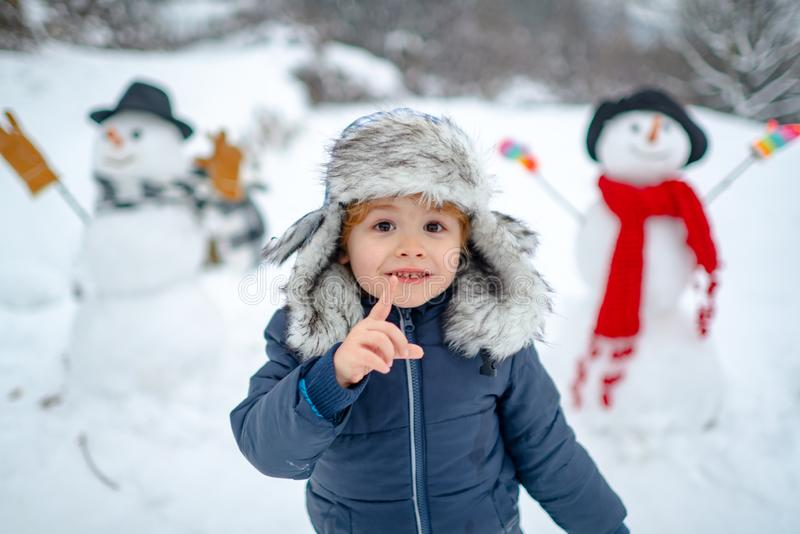 Merry Christmas and Happy new year. Winter portrait of little boy child in snow Garden make snowman. Cute kid - winter royalty free stock photos