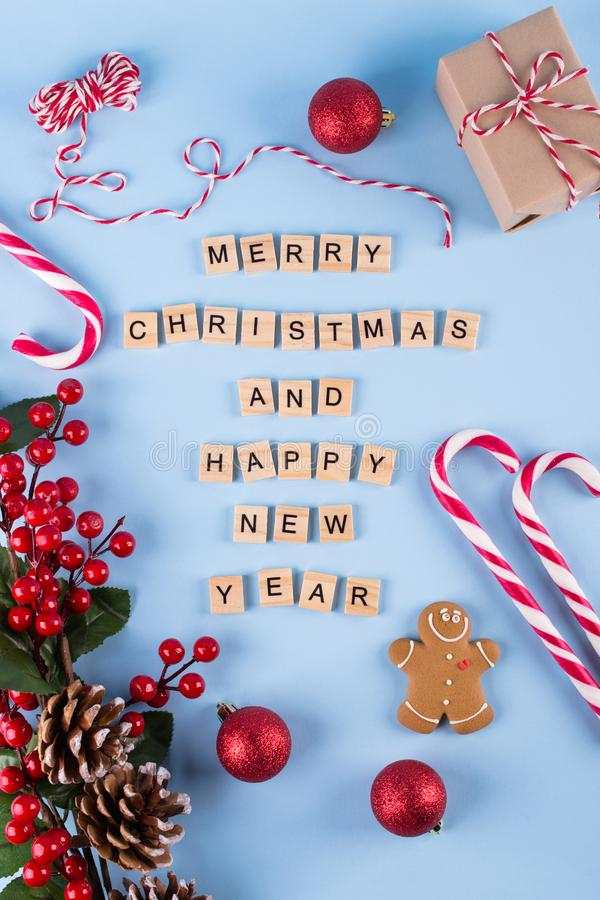 Merry Christmas and happy new year. Words from wooden letters on winter blue background and Christmas decorations. Template, greeting card. Holiday concept royalty free stock photos