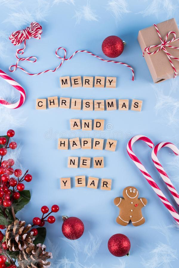 Merry Christmas and happy new year. Words from wooden letters on winter blue background and Christmas decorations. Template, gree. Ting card. Holiday concept royalty free stock photography