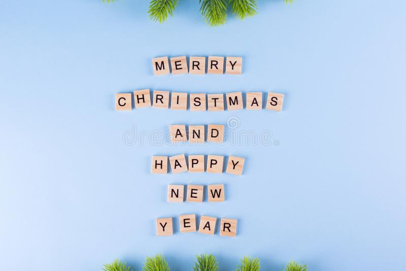 Merry Christmas and happy new year. Words from wooden letters on winter blue background. Template, greeting card. Holiday concept royalty free stock photography